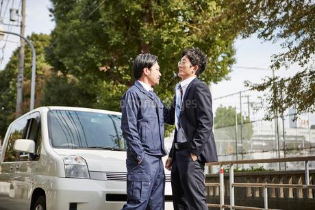車の前で緊迫した二人の男性の写真素材 [FYI02530675]