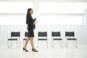 タブレットとコーヒーを持って歩いている女性の写真素材 [FYI02530762]