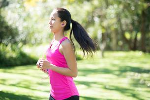 森の中を走っている女性の写真素材 [FYI02530773]
