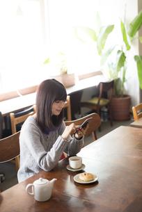 カフェでスマホを見ている女性の写真素材 [FYI02531119]