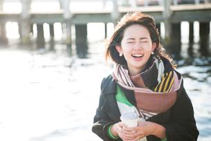 コーヒーを持って笑っている女性の写真素材 [FYI02531230]