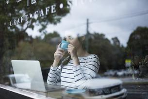 カフェでパソコンを開いてる窓ガラス越しの女性の写真素材 [FYI02531264]