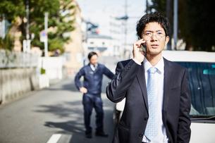車の横に立つ男性と険しい顔で電話をかける男性の写真素材 [FYI02531398]
