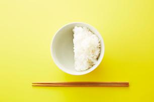 お茶碗に半分だけ入れられたご飯と箸の写真素材 [FYI02531660]