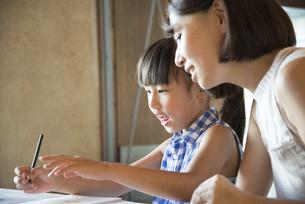 ノートに何か書いている女の子と母親の写真素材 [FYI02531745]
