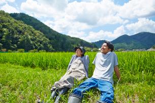 水田の土手で休憩をする男女の写真素材 [FYI02534605]