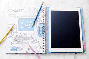 ノートの上に置かれたタブレットと色鉛筆のイラスト素材 [FYI02534920]