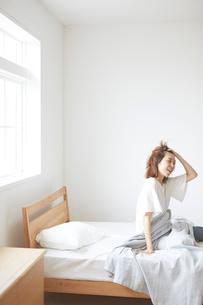 ベッドの上で髪をかき上げて笑う女性の写真素材 [FYI02535235]