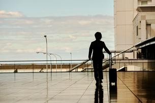 空港にむかうサラリーマンのシルエットの写真素材 [FYI02536350]