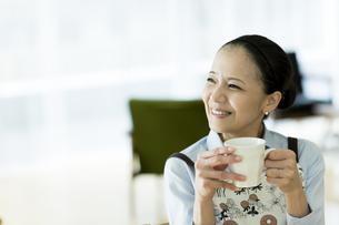 カップを持って笑顔の女性の写真素材 [FYI02537854]