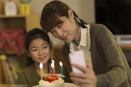 スマートフォンで写真を撮る親子の写真素材 [FYI02537879]