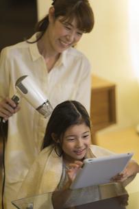 母親にドライヤーで髪を乾かしてもらう娘の写真素材 [FYI02537900]
