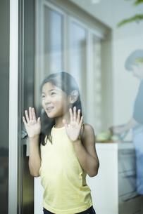 窓辺で外を眺める女の子の写真素材 [FYI02537906]