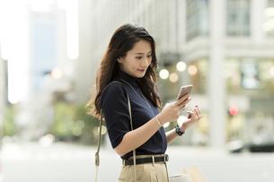 スマートフォンを見る若い女性の写真素材 [FYI02537952]