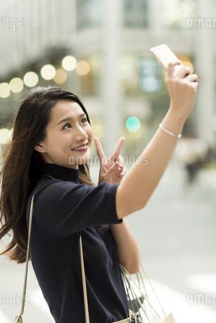 スマートフォンで撮影をする若い女性の写真素材 [FYI02537992]