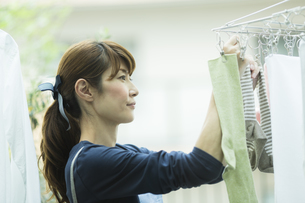 洗濯物を干す女性の写真素材 [FYI02538060]