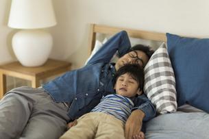 ベッドで眠る父親と息子の写真素材 [FYI02538071]