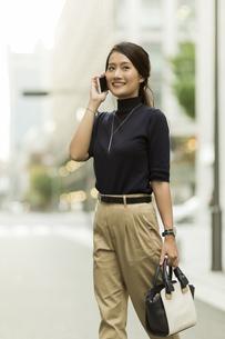 スマートフォンで通話をしながら歩くビジネスウーマンの写真素材 [FYI02538140]