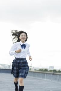 屋上で走る女子学生の写真素材 [FYI02538218]