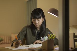 机で勉強をする女の子の写真素材 [FYI02538290]