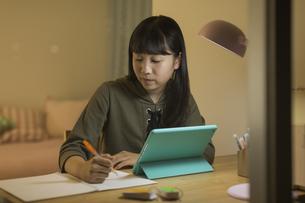 タブレットPCで勉強をする女の子の写真素材 [FYI02538309]