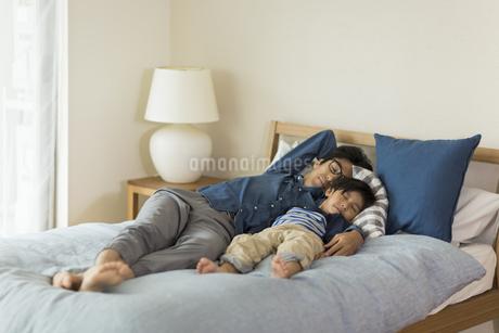 ベッドで眠る父親と息子の写真素材 [FYI02538323]