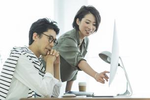 パソコンを見るビジネスマンとビジネスウーマンの写真素材 [FYI02538348]
