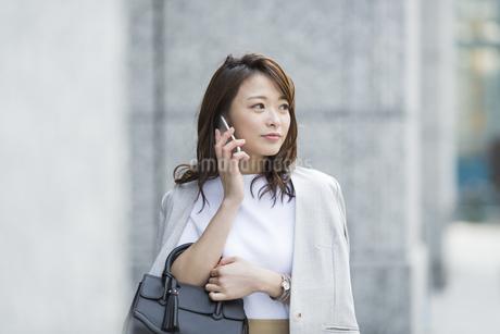 スマートフォンで通話をするビジネスウーマンの写真素材 [FYI02539273]