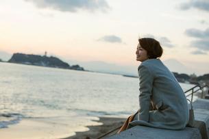 夕焼け空と海を眺める30代女性の写真素材 [FYI02539410]