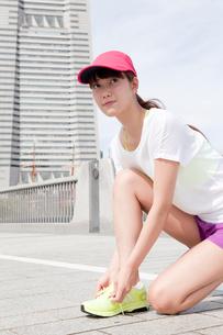 靴の紐を結ぶ若い女性の写真素材 [FYI02539417]