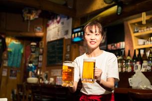 ビールを運ぶ笑顔の居酒屋店員の写真素材 [FYI02539630]