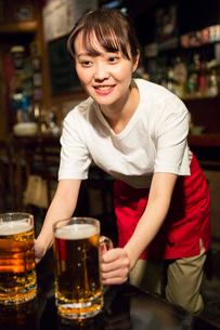 ビールを運ぶ笑顔の居酒屋店員の写真素材 [FYI02539673]