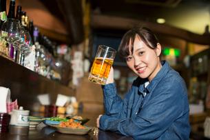 居酒屋で一人飲みを楽しむ20代女性の写真素材 [FYI02539796]