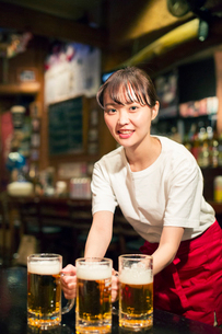 ビールを運ぶ笑顔の居酒屋店員の写真素材 [FYI02539929]