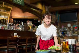 料理を運ぶ笑顔の居酒屋店員の写真素材 [FYI02539990]