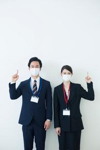 マスクをつけて指差しをするスーツ姿の20代男女の写真素材 [FYI02540118]