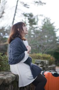 秋の石畳にトランクを置いて本を読む笑顔の女性の写真素材 [FYI02540679]
