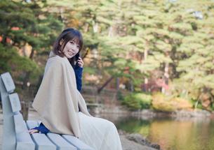 秋の紅葉の公園の池の前のベンチで電話をする女性の写真素材 [FYI02540972]