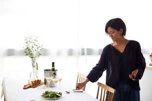 ホームパーティーのテーブルセッティングをする女性の写真素材 [FYI02541058]