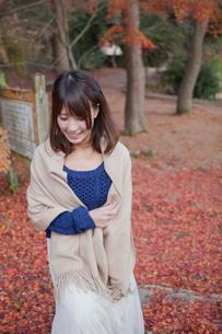 秋の紅葉の落ち葉の上の階段を歩く笑顔の女性の写真素材 [FYI02541097]