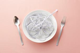 白い皿の上に乗せられたメジャーとシルバーのスプーンとフォークの写真素材 [FYI02541158]