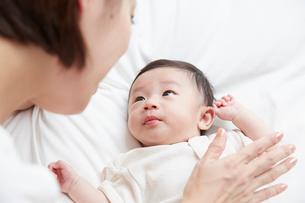 白いシーツの上で寝ている赤ちゃんとお母さんの写真素材 [FYI02543761]