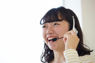 ヘッドフォンをつけて笑顔で話す女性の写真素材 [FYI02543767]
