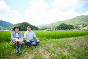 水田の土手に座る笑顔の男女の写真素材 [FYI02543811]