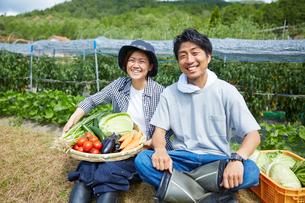 畑の前の土手に座る野菜を持つ男女の写真素材 [FYI02544697]