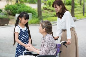 車椅子の祖母に付き添う母娘の写真素材 [FYI02544730]