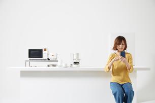 キッチンでスマートフォンを操作する女性の写真素材 [FYI02544941]