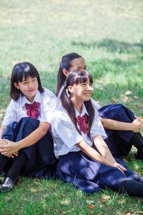 原っぱに背中合わせで座る中学生の写真素材 [FYI02545122]