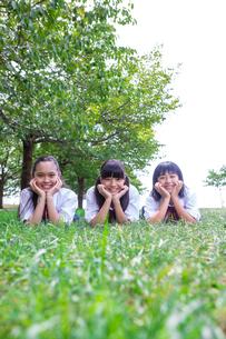草の上にうつぶせで頬杖をつく中学生の写真素材 [FYI02545379]