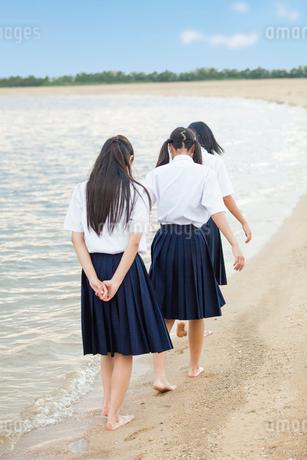 波打ち際を歩く中学生の写真素材 [FYI02545469]